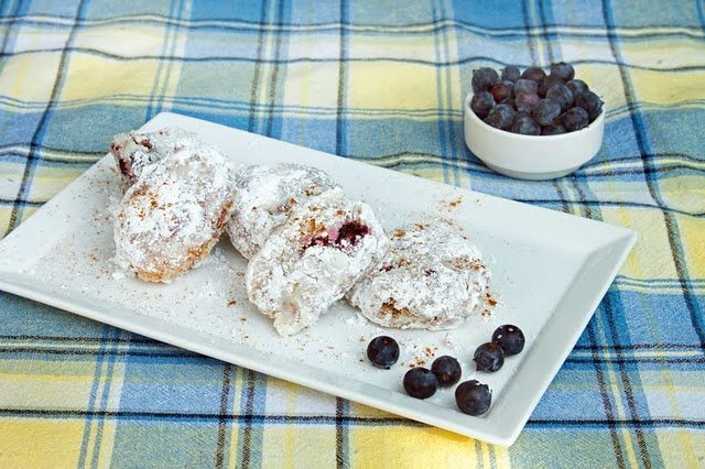 blueberry fritters coated in a powdered sugar sitting on a rectangular white platter next to a bowl of blueberries on a blue and yellow plaid tablecloth