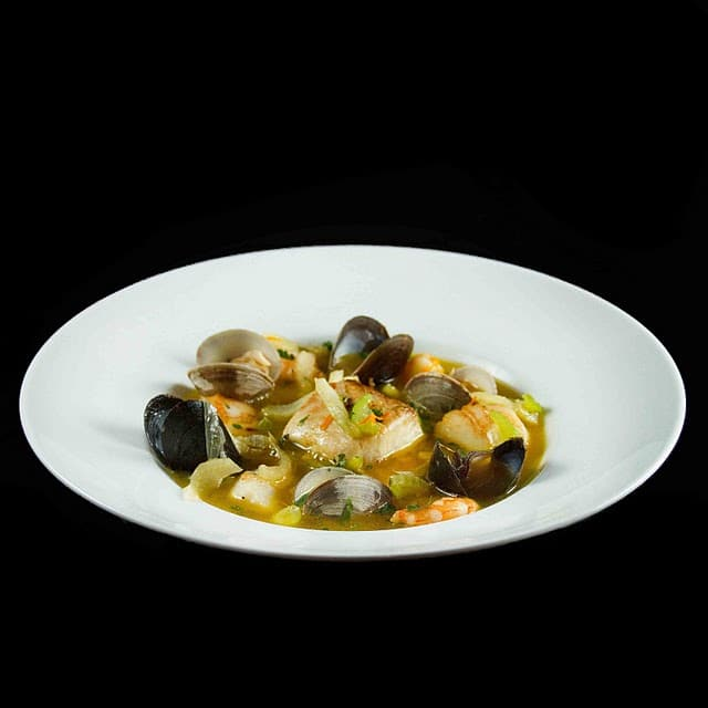 white bowl of bouillabaisse on a black backgroud
