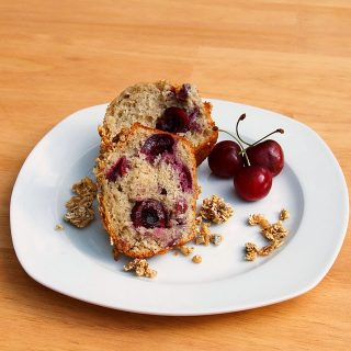 cherry muffin cut in half with 3 cherries on a white plate