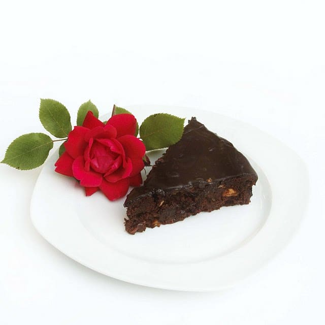 slice of chocolate torte with a rose next to it on a white plate