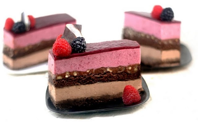 3 slices of entremet on black plates with raspberries