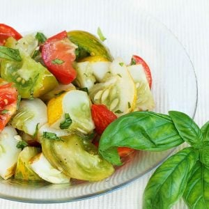 partial view of heirloom tomato salad with a sprig of basil