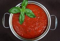 small pot of marinara sauce with a basil garnish sitting on a brown background