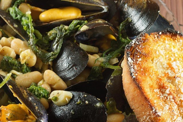 close up of mussels with broccoli rabe and cannellini beans in a large glass bowl with a slice of garlic bread