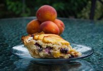 slice of peach blueberry custard pie on a clear glass plate with a stack of peaches behind it