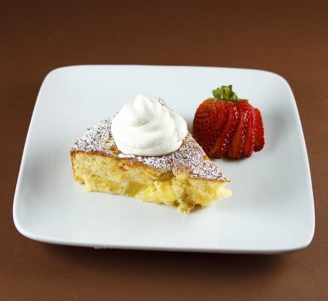 pineapple butter cake with whipped cream sitting on a white plate with strawberry on a brown background