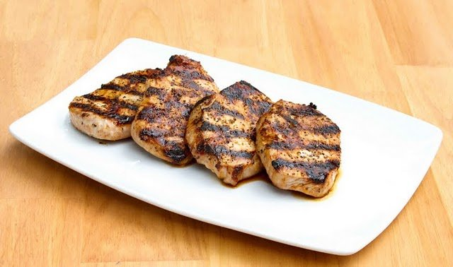 four grilled pork chops on a white platter
