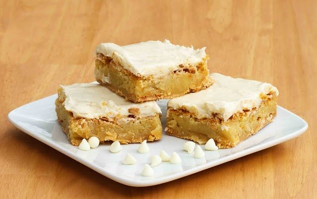 3 iced blondies stacked on a white plate with white chocolate chips