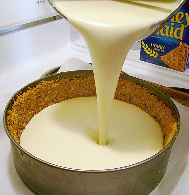 pouring cheesecake batter into s springform pan with a graham cracker crust
