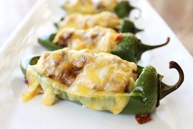 Baked stuffed jalapeno peppers with melted cheese sitting on a white plate