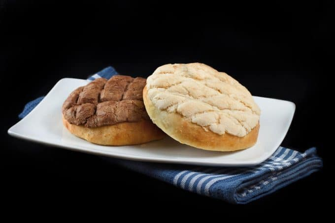 vanilla and chocolate topped pan dulce sitting on a white plate over a blue napkin on a black background