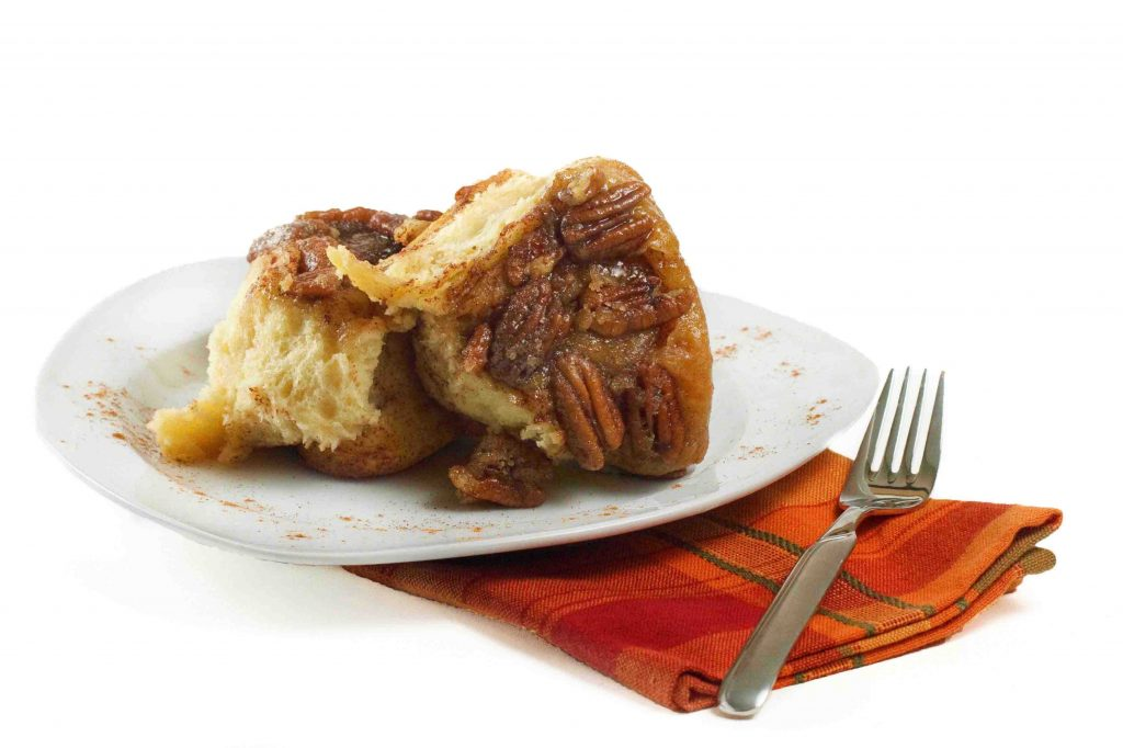 Pecan Caramel Roll on a white plate on top of red checked napkin with a fork2