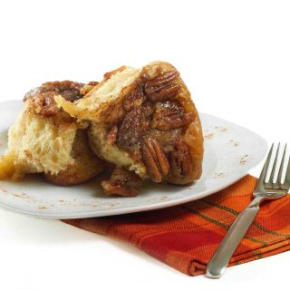 Pecan Caramel Roll on a white plate with a red plaid napkin and a fork