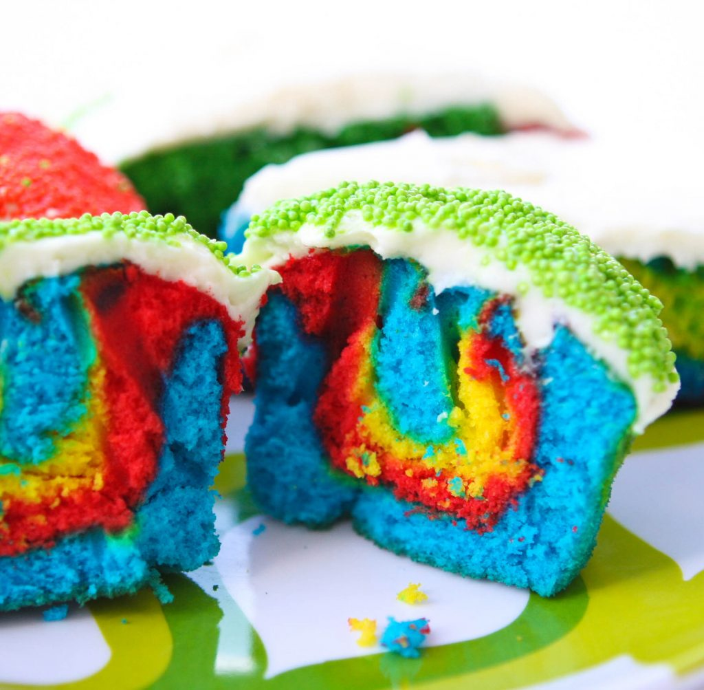 multi colored Rainbow Cupcake cut in half viewed from the front sitting a plate