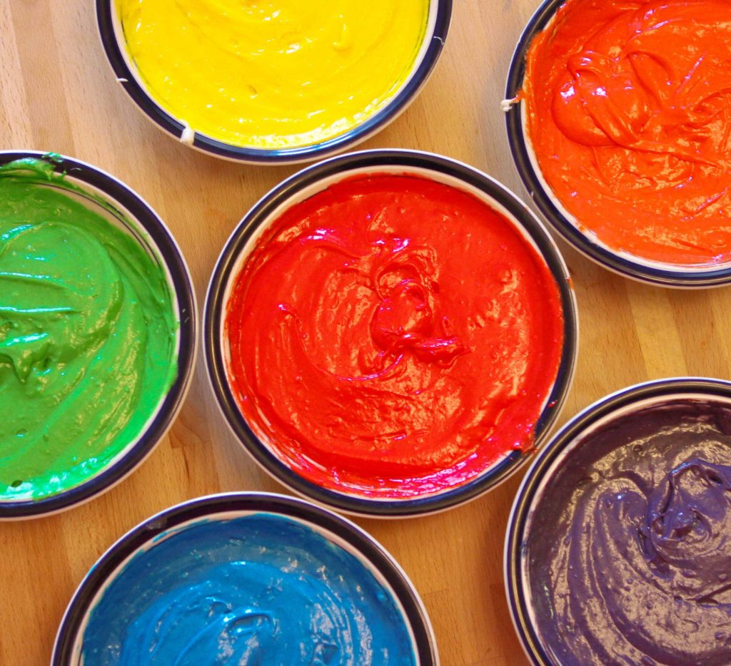 cbrightly colored cake batter divided into bowls of yellow, blue, orange, red , green and purple sitting on a cutting board