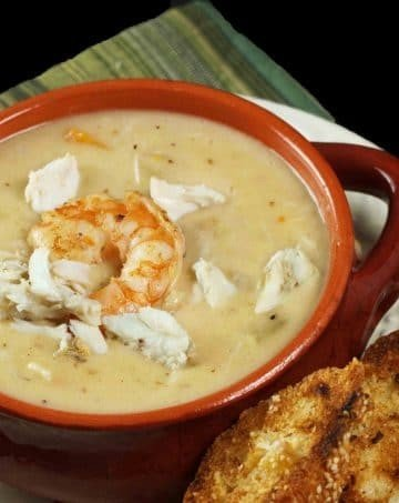 brown crock of shrimp and crab chowder with toasts on a white plate