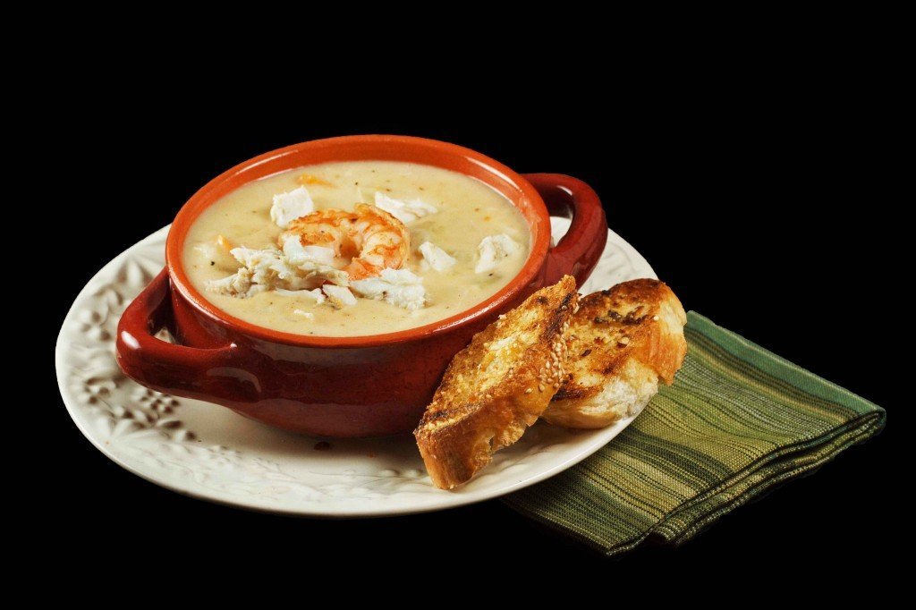 Shrimp and Crab Chowder in a brown crock on a multi colored green napkin on a black background