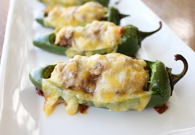 baked stuffed jalapeno peppers sitting on a white plate