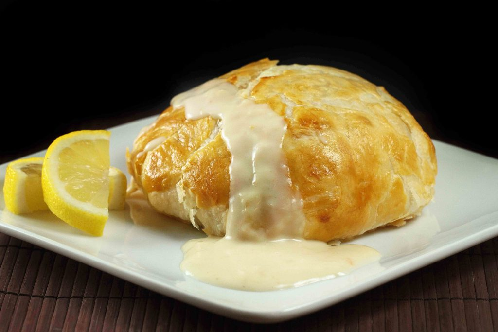 Chicken stuffed with crab meat wrapped in puff pastry, served with a lemon horseradish sauce. Sitting on a white plate