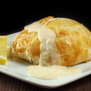 stuffed chicken wrapped in golden brown pastry dough on a white plate with a cream sauce