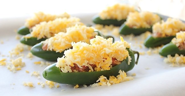 jalapeno pepper halves stuffed and topped with cheese sitting on a white plate