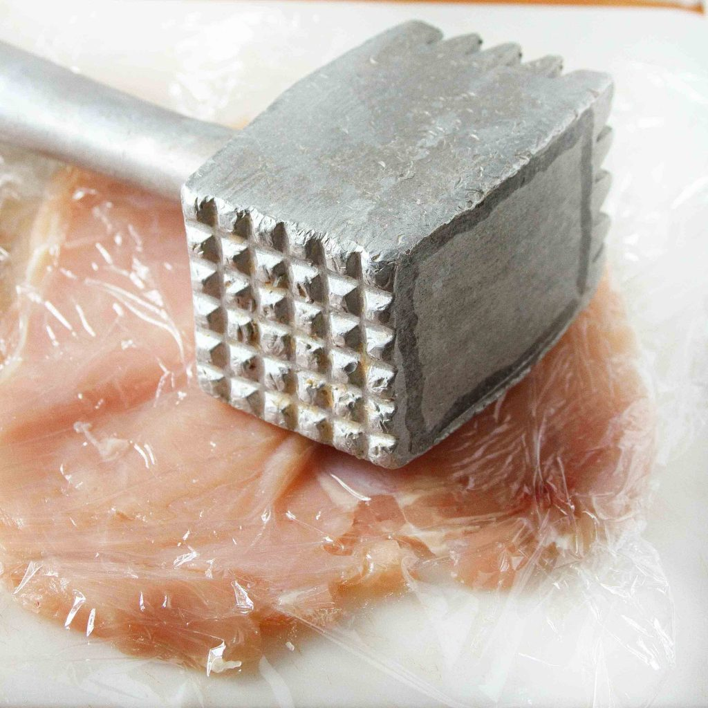 chicken breast between plastic wrap on a cutting board with a meat hammer sitting on top