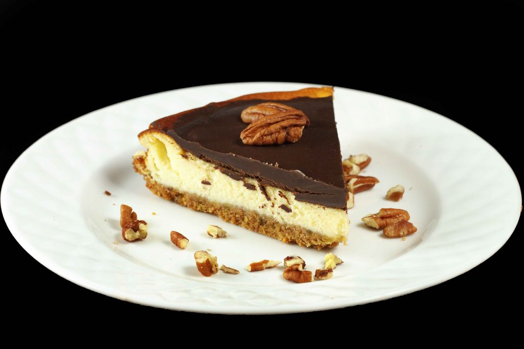 slice of Feta Cheesecake topped with chocolate ganache served on a white plate with crumbled pecans