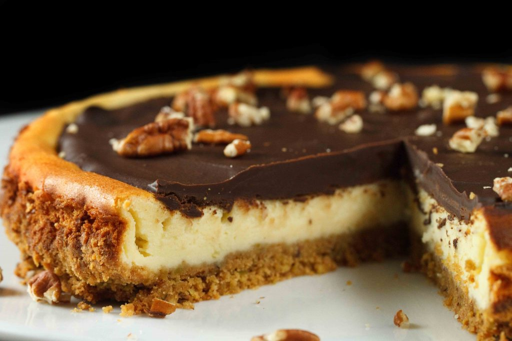 chcocolate topped Feta Cheesecake topped with pecans with a graham cracker crust sitting on a white plate