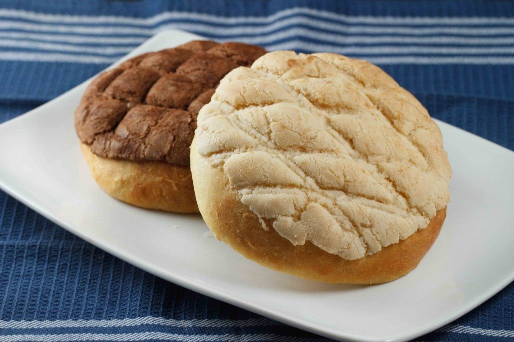 a vanilla pan dulce resting on a chocolate pan dulce on a white plate sitting on a blue napkin