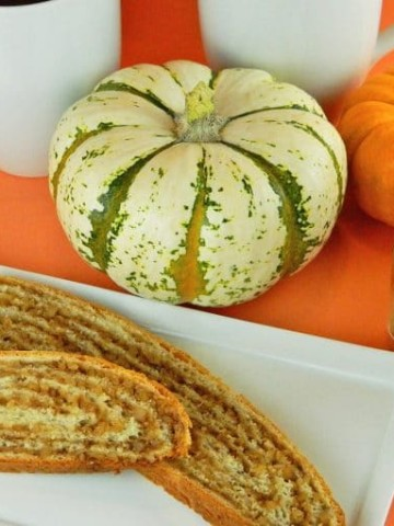 slices of potica on a white platter next to small multi-colored pumpkins