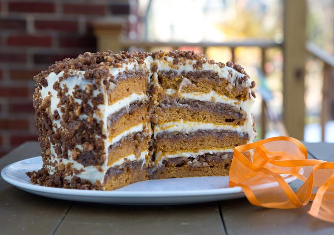 whole pumpkin crunch cake with slices taken out on a white platter with an orange ribbon