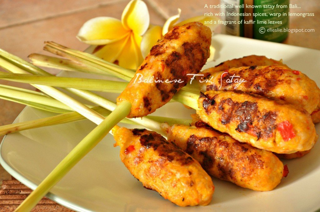 Balinese fish satay on a white platter with a flower in the backgroud