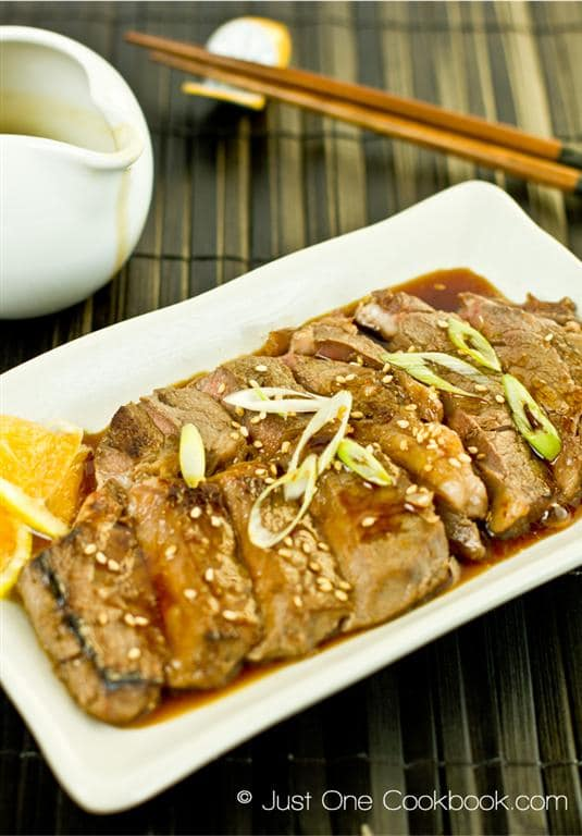 white oblong plate of beef teriyaki on a tray with pitcher of sauce and chopsticks