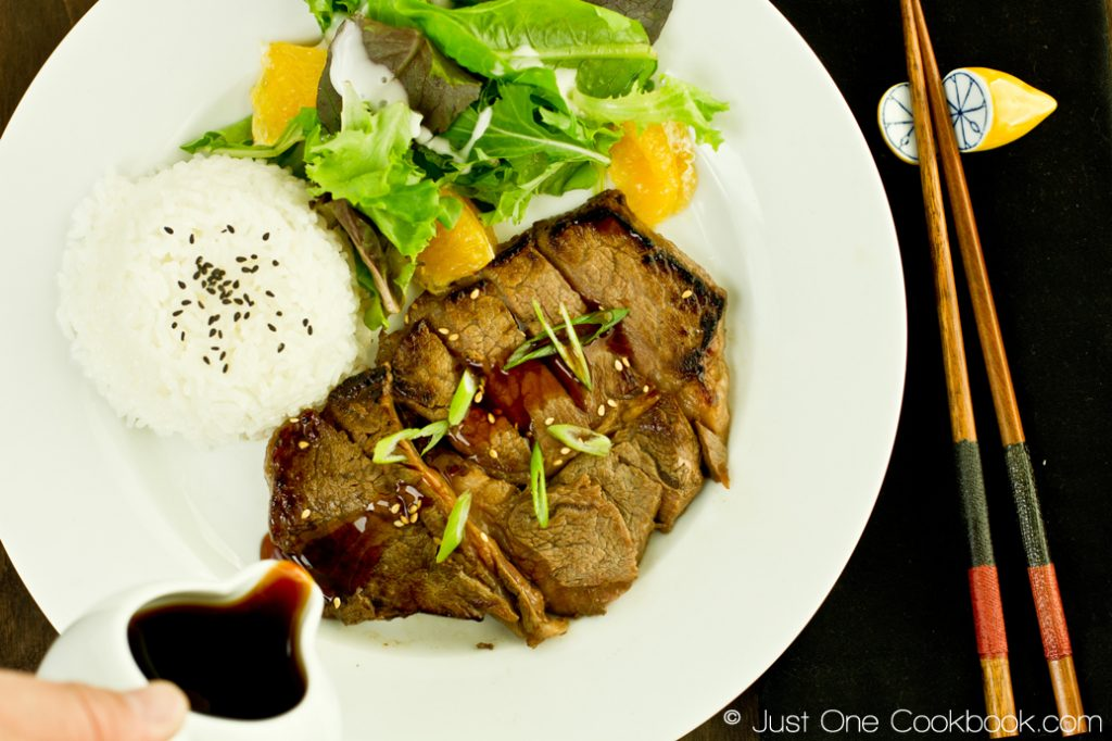 beef teriyaki on a white plate with rice and salad along side a pitcher of sauce and chopsticks