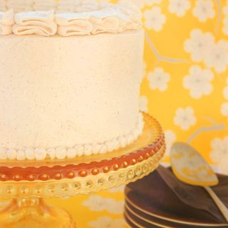 partial view of pumpkin marshmallow brown butter cake on a cake stand
