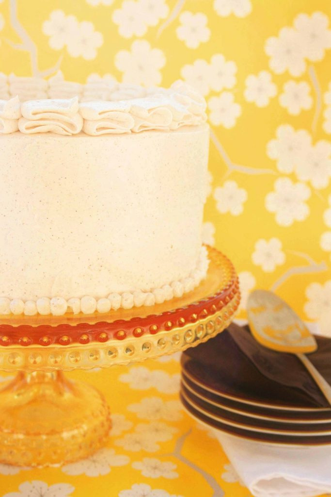 partial view of an iced Pumpkin Marshmallow Brown Butter Cake on a pedestal in front of happy yellow wall paper