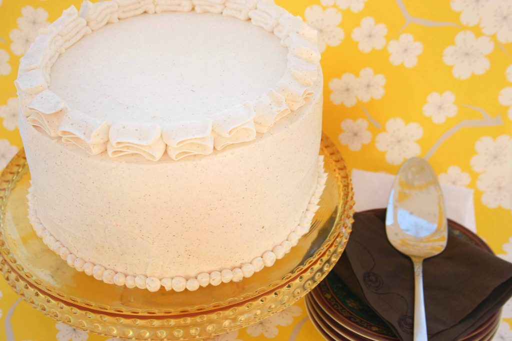view of an iced Pumpkin Marshmallow Brown Butter Cake on a pedestal in front of happy yellow wall paper