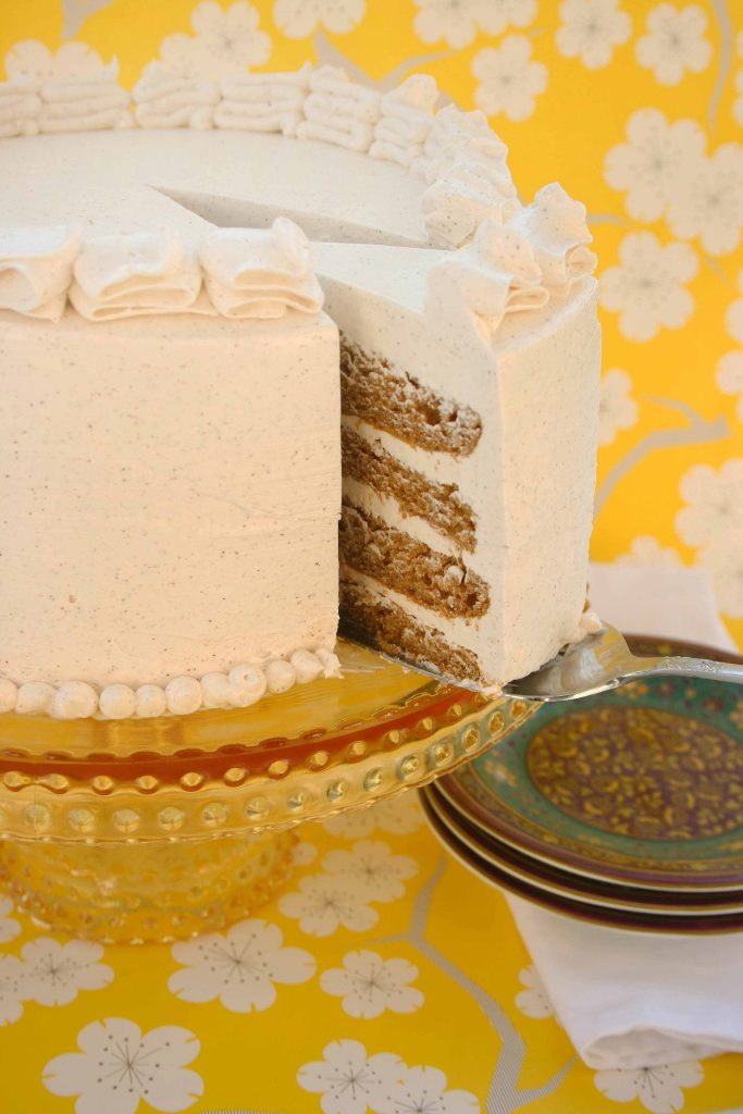 cutting a slice out of an iced Pumpkin Marshmallow Brown Butter Cake on a pedestal in front of happy yellow wall paper