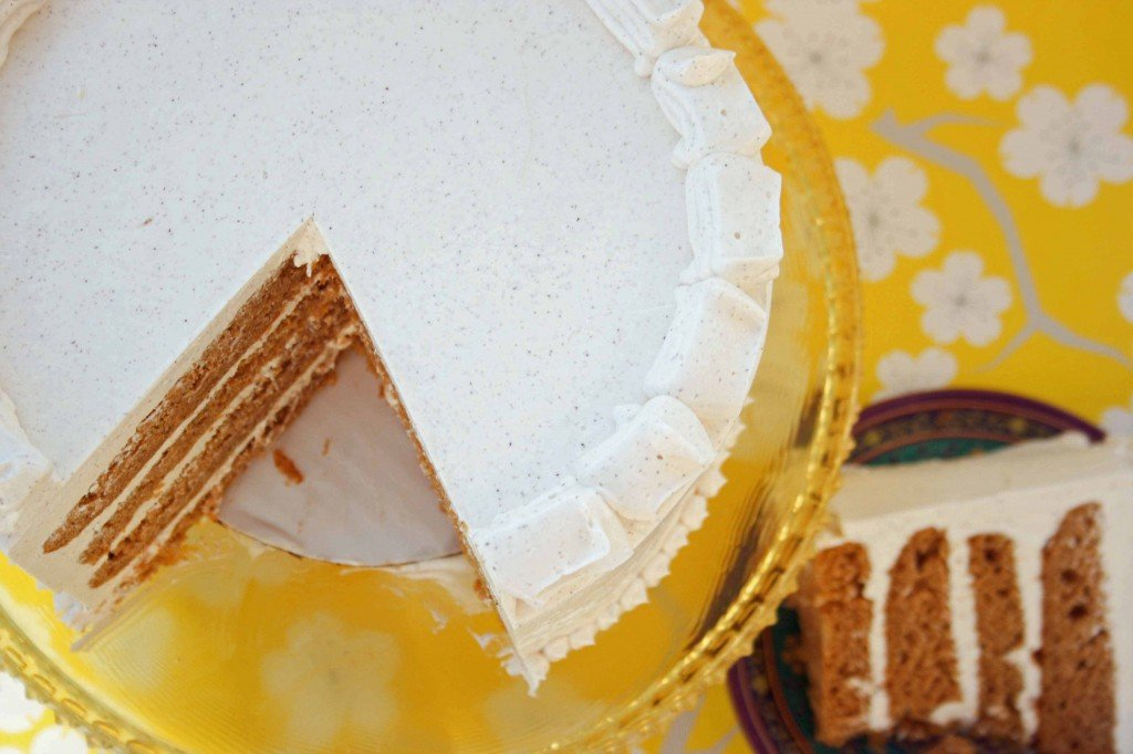 partial view of pumpkin marshmallow brown butter cake on a cake stand with a slice cut out