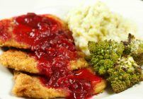 close up of turkey Milanese with a cranberry sauce next to romanesco and mashed potatoes