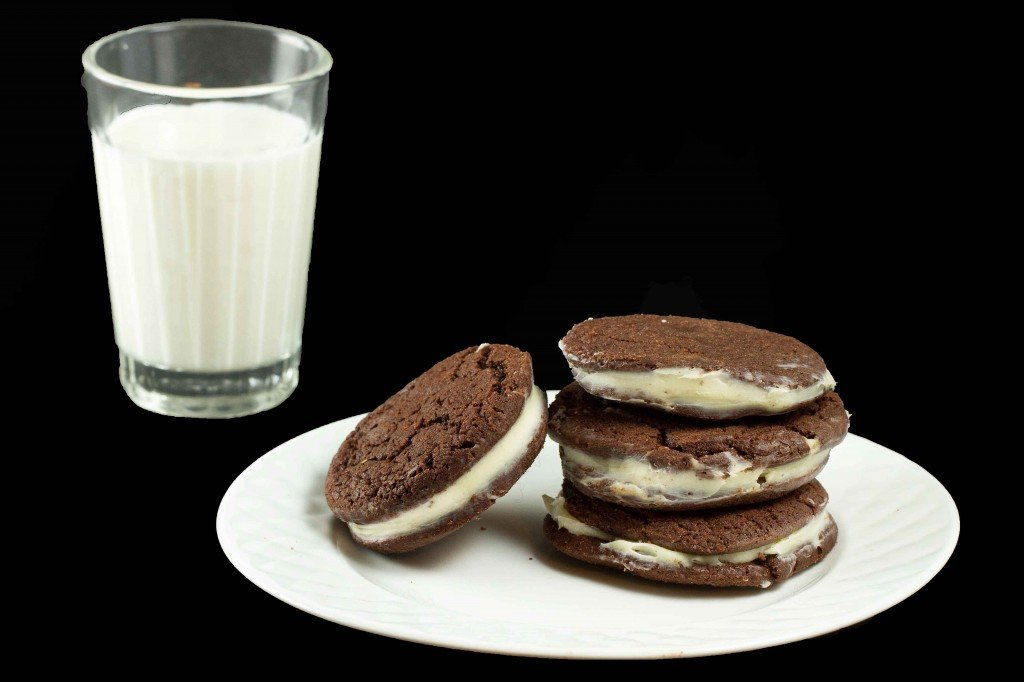 stack of triple chocolate cookies on a white plate next to a glass of milk