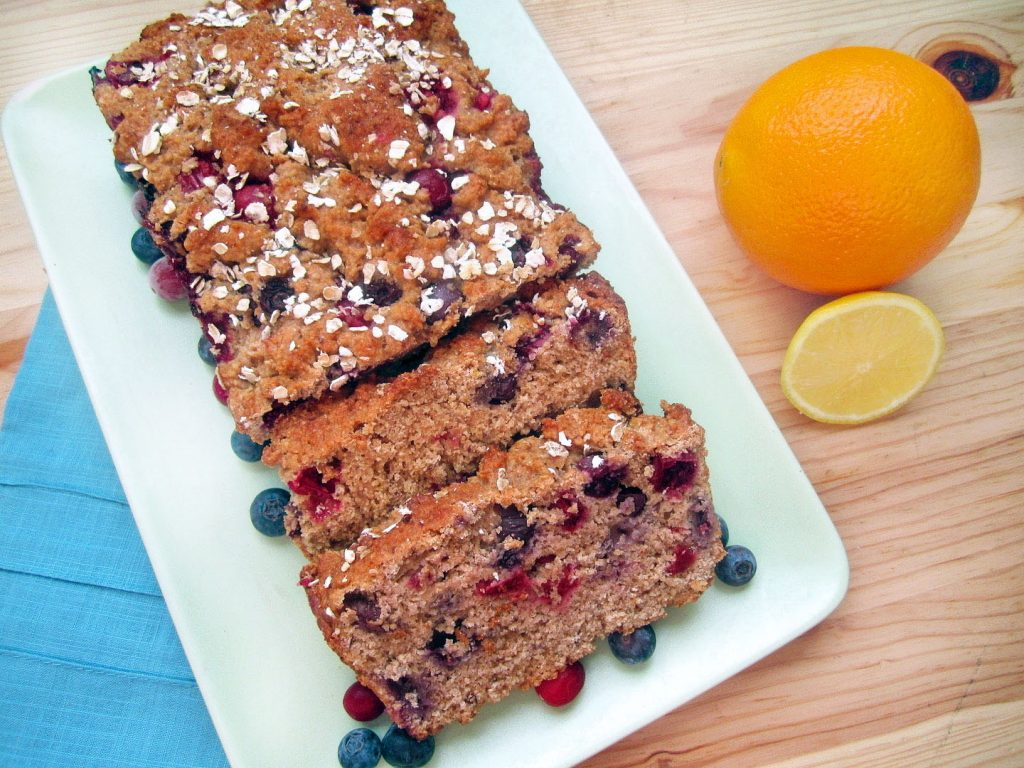 Berry Citrus Bread on a white plate with a blue napkin under the plate and an orange next to the plate