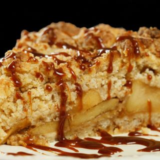 slice of caramel apple torte drizzled with caramel sauce on a white plate