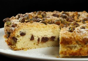 ricotta chocolate chip cake with slice cut out, sitting on a white plate