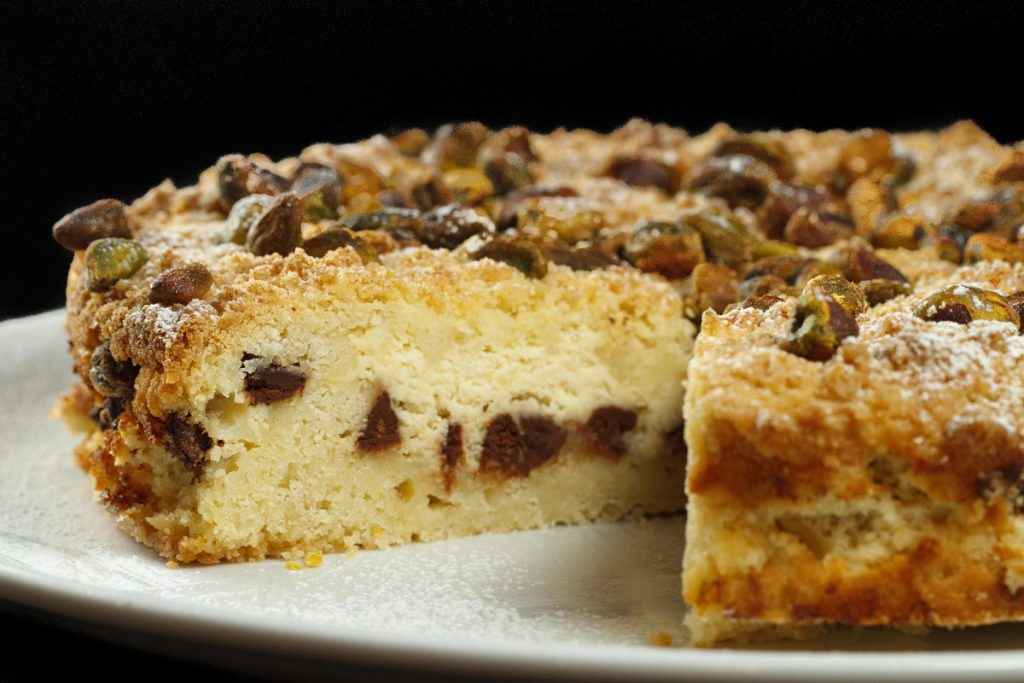 ricotta chocolate chip cake with a slice out showing the inside of the cake on a white plate