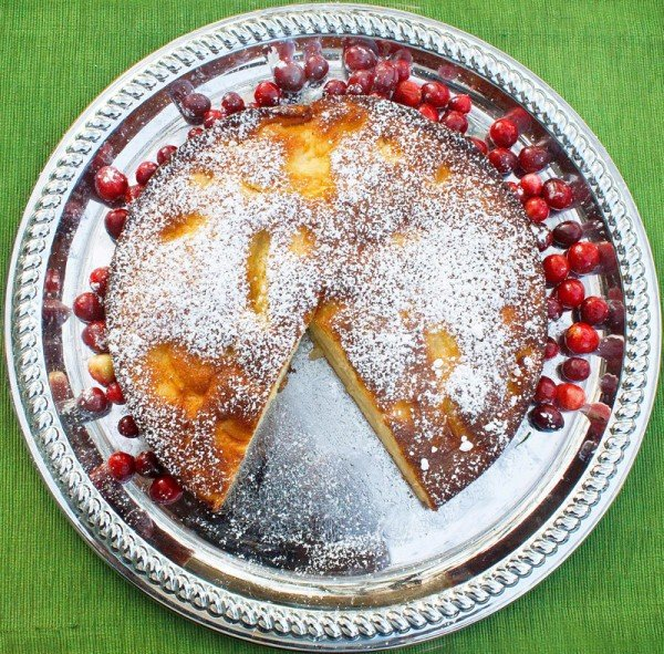 overhead view of torta di mele on a silver platter with a slice cut out