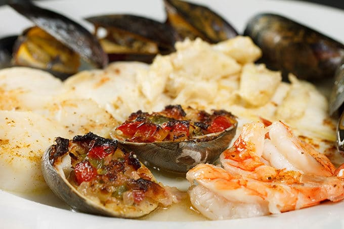 side view of broiled seafood combo on a white plate