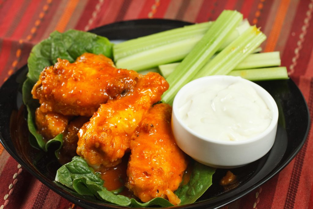 honey lime buffalo wings with blue cheese dressing and celery sticks on a black plate on a multi colored table cloth