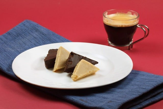 slices of dark chocolate and white chocolate pate on a white plate on a blue napkin with a cup of espresso on a red background