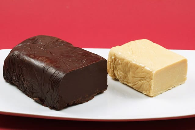 loaf of dark chocolate pate and loaf of white chocolate pate on a white plate on a red backgrounc